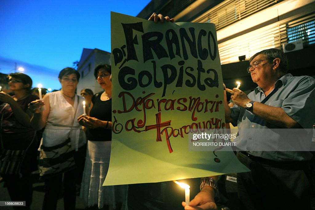 Supporters of ousted Paraguayan President Fernando Lugo and relatives of jailed peasants hold a sign reading 'Franco, in favour of the coup, will you let more Paraguayans die?', as they remain on vigil in demand of their freedom on November 21, 2012 in Asuncion. Four peasants accused -alongside other eight people- of the death of six policemen past June 15 in Curuguaty, 250 km northeast of Asuncion, remain on hunger strike. 11 peasants died in the confrontation with the police during the eviction of a private property. AFP PHOTO/ Norberto Duarte