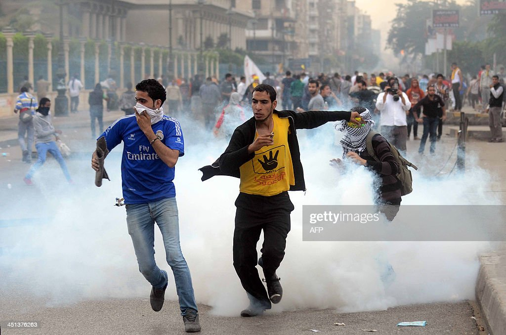 Supporters of ousted president Mohamed Morsi and the Muslim brotherhood run away from tear gas during clashes with Egyptian riot police close to...