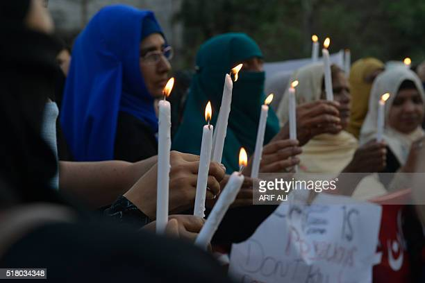 Supporters of Pakistan Awami Tehreek hold lighted candles as they stage a rally in Lahore on March 29 to pay tribute for the victims of a suicide...