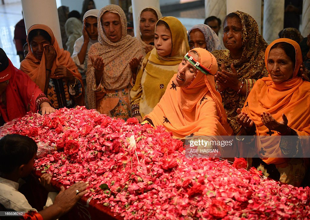 Supporters of Pakistan People's Party (PPP) pray over the grave of former premier Zulfiqar Ali Bhutto, father of Pakistan's slain former premier Benazir Bhutto, at the family mausoleum in Garhi Khuda Bukash near Larkana on April 4, 2013, on his death anniversary. Supporters of Pakistan People's Party (PPP) of Bhutto arrived at her hometown in southern Sindh province to pay homage to Pakistan's former Prime Minister Zulfiqar Ali Bhutto who was hanged by the country's late military dictator General Zia ul Haq on April 4, 1979. AFP PHOTO/Asif HASSAN