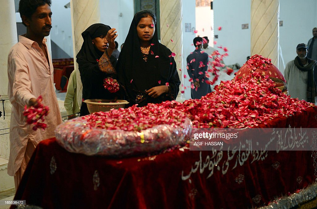 Supporters of Pakistan People's Party (PPP) showers rose petals on the grave of former premier Zulfiqar Ali Bhutto, father of Pakistan's slain former premier Benazir Bhutto, at the family mausoleum in Garhi Khuda Bukash near Larkana on April 4, 2013, on his death anniversary. Supporters of Pakistan People's Party (PPP) of Bhutto arrived at her hometown in southern Sindh province to pay homage to Pakistan's former Prime Minister Zulfiqar Ali Bhutto who was hanged by the country's late military dictator General Zia ul Haq on April 4, 1979. AFP PHOTO/Asif HASSAN