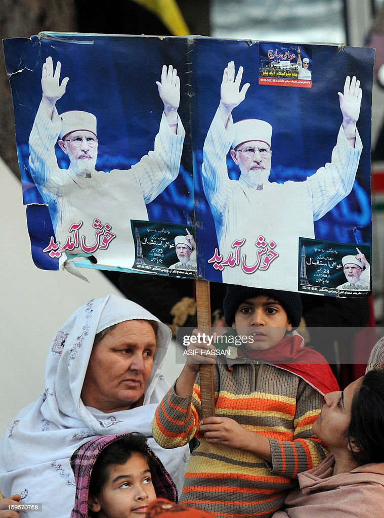 Supporters of Pakistani cleric Tahir-ul Qadri hold placards with his portrait on the third day of the protest rally in Islamabad on January 16, 2013. A populist cleric Wednesday urged Pakistani politicians to join tens of thousands taking part in the largest protest in Islamabad for years, ratcheting up the pressure on the government to step down. AFP PHOTO/Asif HASSAN