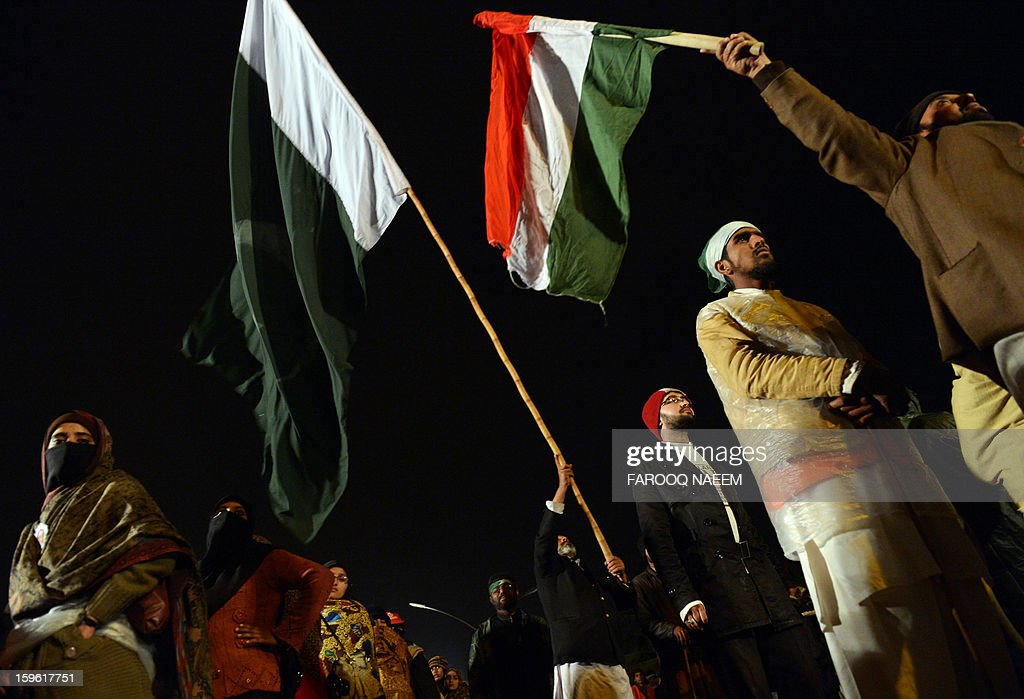 Supporters of Pakistani Muslim cleric Tahir-ul Qadri wave national flags as they celebrate the victory of their demand for electoral reform at a protest rally in Islamabad on January 17, 2013, as ruling patry Information Minister Qamar Zaman Kaira (Center L) and Law Minister Farooq Naek look on besides him. A populist Pakistani cleric calling for electoral reforms announced that a mass sit-in of tens of thousands of people camped outside parliament in Islamabad would end today. Qadri wants parliament dissolved and a caretaker government set up in consultation with the military and judiciary to implement key reforms before free elections can be held. AFP PHOTO / Farooq NAEEM