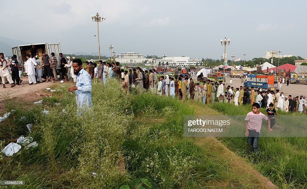Supporters of Pakistani opposition politician Imran Khan and populist cleric Tahir-ul-Qadri wait in line to receive food while gathered at an anti-government protest site in Islamabad on August 22, 2014. Pakistani opposition politician Imran Khan called August 21 off talks with the government aimed at ending protests seeking the fall of the prime minister, which have unnerved the nuclear-armed nation. Khan and populist cleric Tahir-ul-Qadri have led followers protesting outside parliament for the past two days demanding Prime Minister Nawaz Sharif quit. AFP PHOTO/Farooq NAEEM