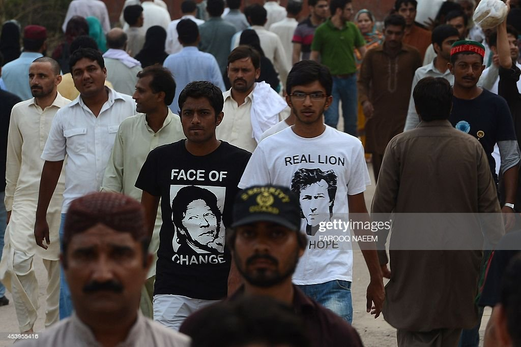 Supporters of Pakistani opposition politician Imran Khan wear T-shirts with his portrait as they arrive at an anti-government protest site in Islamabad on August 22, 2014. Pakistani opposition politician Imran Khan called August 21 off talks with the government aimed at ending protests seeking the fall of the prime minister, which have unnerved the nuclear-armed nation. Khan and populist cleric Tahir-ul-Qadri have led followers protesting outside parliament for the past two days demanding Prime Minister Nawaz Sharif quit. AFP PHOTO/Farooq NAEEM