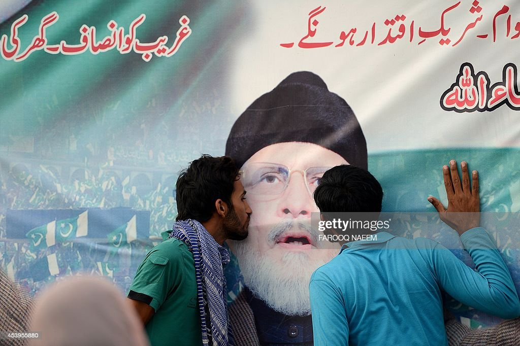 Supporters of Pakistani populist cleric Tahir-ul-Qadri kiss his portrait on a banner hung at an anti-government protest site in front of the Parliament in Islamabad on August 22, 2014. Pakistani opposition politician Imran Khan called August 21 off talks with the government aimed at ending protests seeking the fall of the prime minister, which have unnerved the nuclear-armed nation. Khan and populist cleric Tahir-ul-Qadri have led followers protesting outside parliament for the past two days demanding Prime Minister Nawaz Sharif quit. AFP PHOTO/Farooq NAEEM