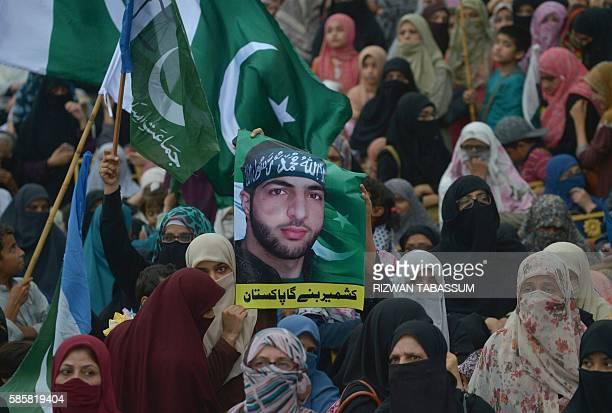 Supporters of Pakistan's Islamist party JamaateIslami carry a poster bearing the image of slain Indian Kashmiri Hizbul Mujahideen commander Burhan...