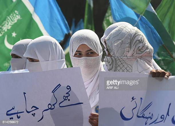 Supporters of Pakistan's Islamist party JamaateIslami hold placards during a rally to mark International Women's Day in Lahore on Marchi 8 2016 Women...