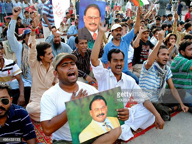 Supporters of Pakistan's Muttahida Qaumi Movement party hold photographs of their party leader Altaf Hussain as they chant slogans in Hyderabad some...
