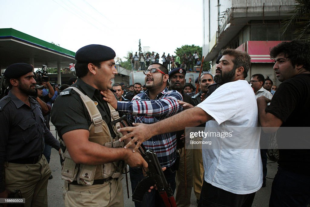 Supporters of Pakistan's Tehreek-e-Insaf (PTI) chairman Imran Khan, right, scuffle with police officers during a demonstration in Karachi, Pakistan, on Monday, May 13, 2013. Nawaz Sharif was headed for a record third term as prime minister of Pakistan as unofficial results from a landmark election gave him the convincing win he sought to tackle a slumping economy and growing militancy. Photographer: Asim Hafeez/Bloomberg via Getty Images Photographer: Asim Hafeez/Bloomberg via Getty Images