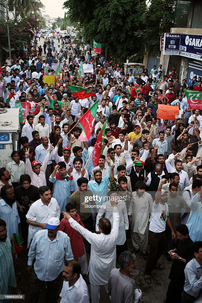 Supporters of Pakistan's Tehreek-e-Insaf (PTI) chairman Imran Khan wave flags and shout slogans during a demonstration in Karachi, Pakistan, on Monday, May 13, 2013. Nawaz Sharif was headed for a record third term as prime minister of Pakistan as unofficial results from a landmark election gave him the convincing win he sought to tackle a slumping economy and growing militancy. Photographer: Asim Hafeez/Bloomberg via Getty Images