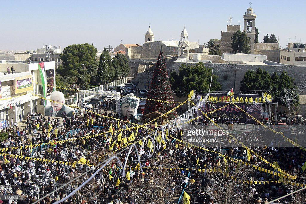 Supporters of Palestinian leader Mahmud Abbas gather and wave the Fatah movement flag in front of the Church of the Nativity in the West Bank city of Bethlehem, on December 31, 2012, during celebrations marking the 48th anniversary of the movement's founding.