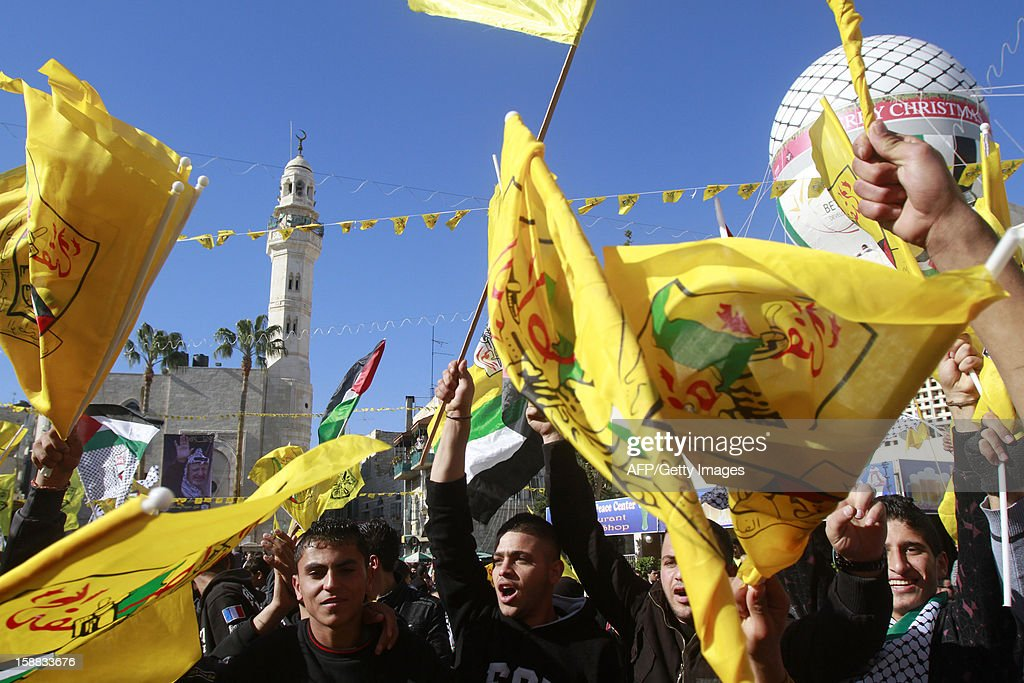 Supporters of Palestinian leader Mahmud Abbas wave the Fatah movement flag in front of the Church of the Nativity in the West Bank city of Bethlehem, on December 31, 2012, during celebrations marking the 48th anniversary of the movement's founding. AFP PHOTO/MUSA AL SHAER