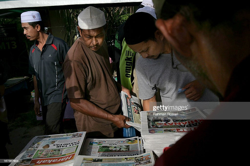 Supporters of Pan Islamic Party' checks out the headlines of the newspapers at a morning market on April 26, 2013 in Rusila, Malaysia. Malaysia's 13th general election will be held on May 5.