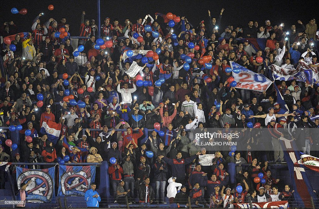 Supporters of Paraguay's Cerro Porteno cheer their team during their Copa Libertadores 2016 round before the quarterfinals second leg football match against Argentina's Boca Juniors at La Bombonera stadium in Buenos Aires, Argentina, on May 5, 2016. / AFP / ALEJANDRO