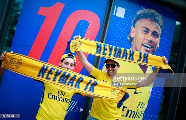 TOPSHOT Supporters of ParisSaintGermain's new signing Neymar pose with scarves outside the ParisSaintGermain football club store on the Champs...