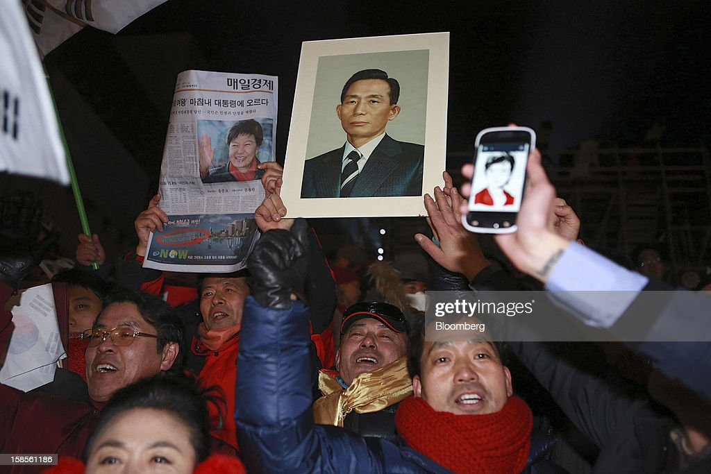 Supporters of Park Geun Hye, the president-elect from the ruling New Frontier Party, celebrate as they also hold a portrait of Park's father, the late president Park Chung Hee, center, in Seoul, South Korea, on Thursday, Dec. 20, 2012. Park was elected president of South Korea, becoming the first woman to lead Asia's fourth- biggest economy more than 30 years after her father's reign as dictator ended with his assassination. Photographer: Jean Chung/Bloomberg via Getty Images
