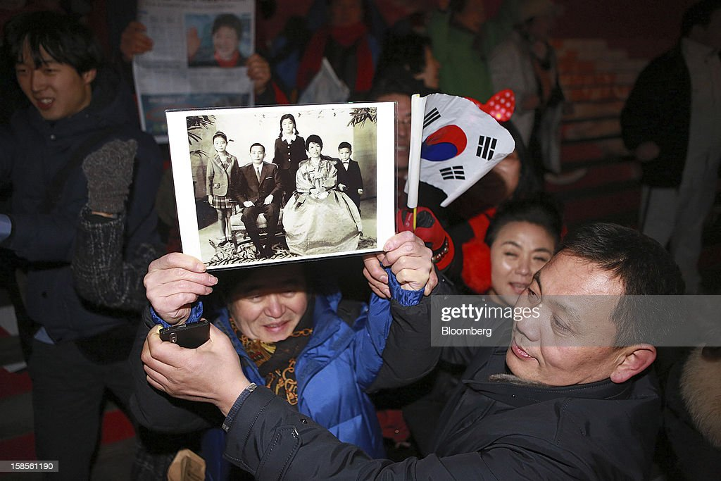 Supporters of Park Geun Hye the presidentelect from the ruling New Frontier Party celebrate while holding a family portrait of the late president...