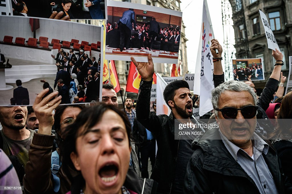 Supporters of People's Democratic Party (HDP) hold pictures of mass brawl at the parlement and shout slogans against the goverment on May 4 ,2016 during a protest in Istanbul. Ruling party and opposition Turkish lawmakers on May 2, 2016 exchanged punches and hurled water bottles at each other as a new mass brawl erupted in parliament over changes to the constitution, television broadcasts showed. / AFP / OZAN