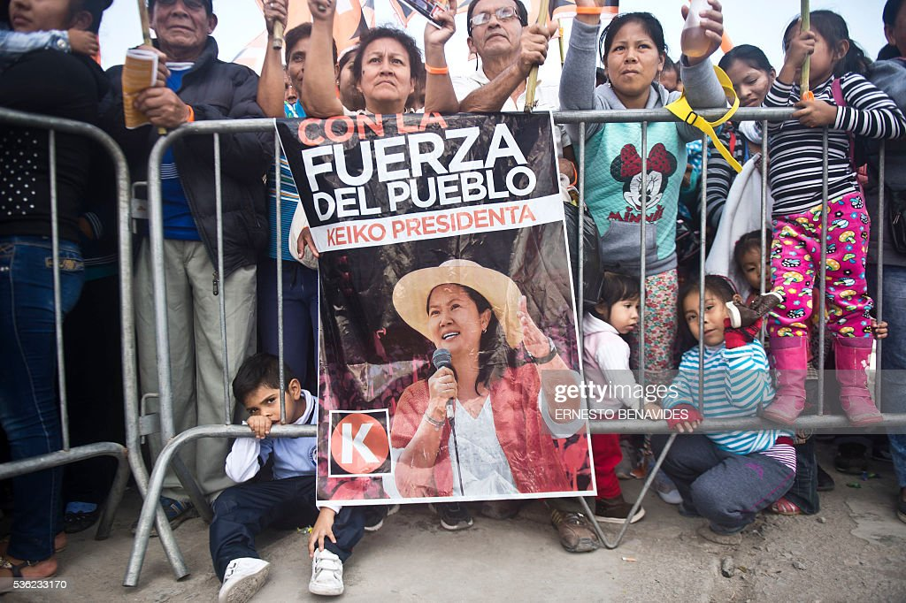 Supporters of Peruvian presidential candidate for the Fuerza Popular (Popular Force) party and daughter of imprisoned former Peruvian President (1990-2000) Alberto Fujimori, Keiko Fujimori, attend a campaign rally in Lima on May 31, 2016. Fujimori leads the polls for next May 5 presidential elections in Peru. The poster reads 'With the people's strength. Keiko President'. / AFP / ERNESTO