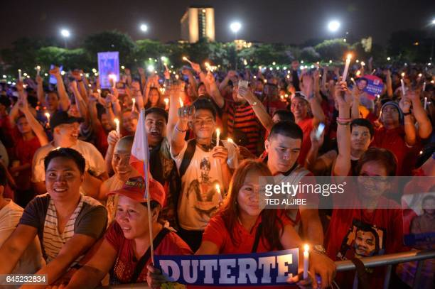 Supporters of Philippine President Rodrigo Duterte raise clinched fists as they hold candles during a rally at a park in Manila on February 25...