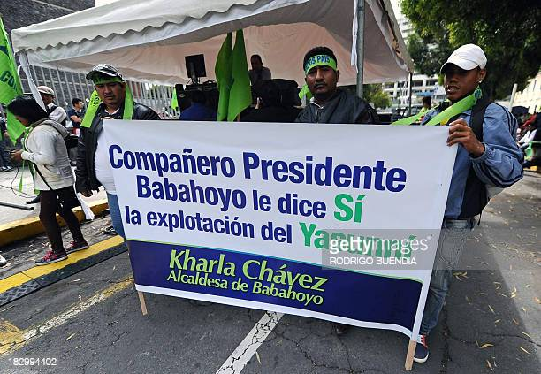 Supporters of President Rafael Correa backing oil drilling in the Yasuni National Park hold banners outside the National Assembly building in Quito...
