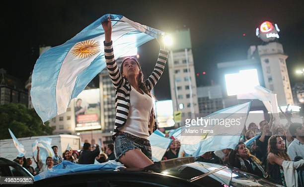 Supporters of Presidentelect Mauricio Macri wave Argentinian flags in the street celebrating after he defeated ruling party candidate Daniel Scioli...