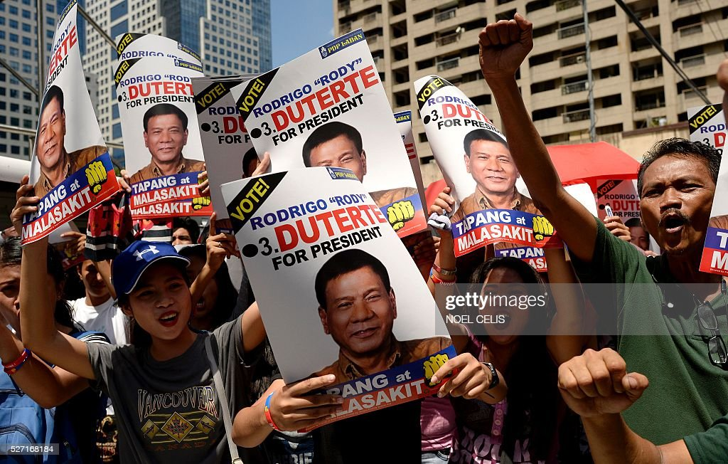 Supporters of Presidential candidate and Davao Mayor Rodrigo Duterte hold a protest near the premises of the Bank of the Philippine Island (BPI) in Manila on May 2, 2016. Independent vice presidential candidate Antonio Trillanes has accused leading presidential candidate Rodrigo Duterte of hiding unexplained wealth deposited in secret accounts in the BPI and dared Duterte to open his bank records for public scrutiny. / AFP / NOEL