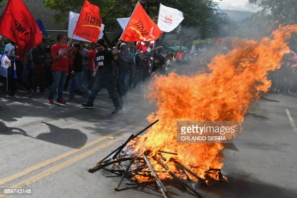 Supporters of presidential candidate for Honduras' Opposition Alliance against Dictatorship Salvador Nasralla set on fire campaign posters of...