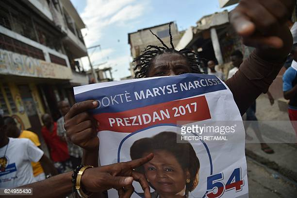 TOPSHOT Supporters of presidential candidate Maryse Narcisse of Lavalas display party posters during a march in support of their candidate in...