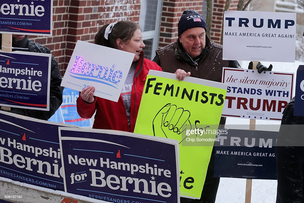 Supporters of presidential candidates Sen. Bernie Sanders (I-VT) and Donald Trump visit while holding signs outside the polling place at the Webster School February 9, 2016 in Manchester, New Hampshire. Tuesday is the 100th anniversary of the New Hampshire primariy, the 'First in the Nation' test for presidential candidates from both parties.