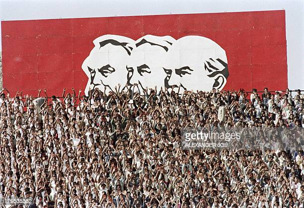 Supporters of procommunist Ethiopian Workers' party wave in front of a huge portraits of the founders of the 'scientific socialism' Karl Marx...