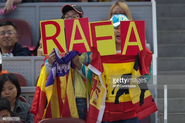 Supporters of Rafael Nadal of Spain shout his name during his men's singles match against Lucas Pouille of France at the China Open tennis tournament...