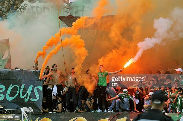 Supporters of Raja Casablanca football club wave flares during riots between fans and the police following a football match between Wydad Casablanca...