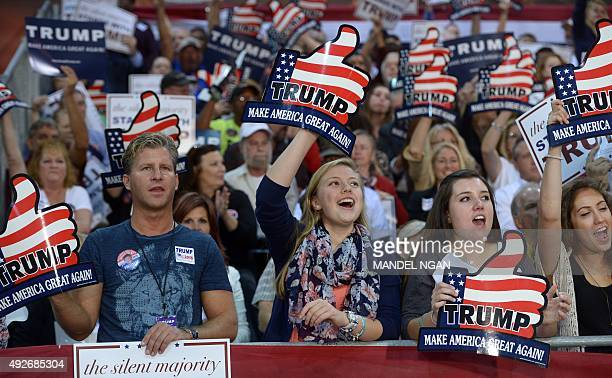 Supporters of Republican presidential candidate Donald Trump wave banners during a rally at the Expo Hall of the Richmond International Raceway on...
