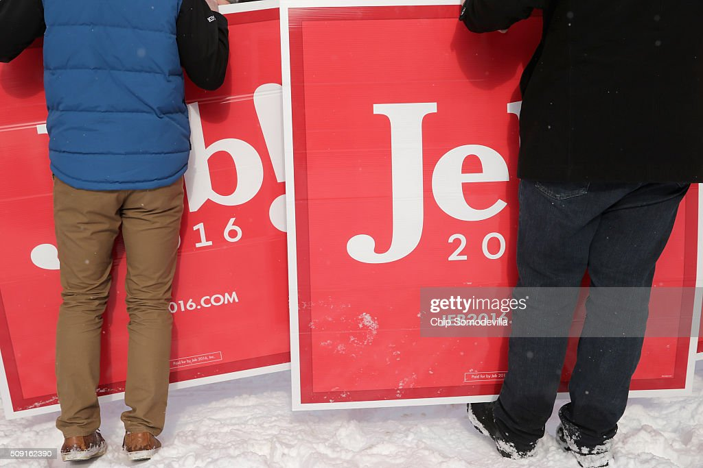 Supporters of Republican presidential candidate Jeb Bush hold campaign signs while waiting for Bush outside the polling place at Webster School on primary day February 9, 2016 in Manchester, New Hampshire. Candidates from both parties are making last-minute attempts to swing voters to their side on the day of the 'First in the Nation' presidential primary.