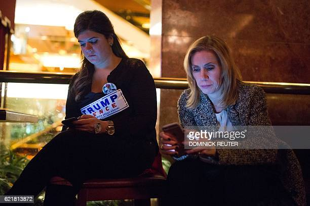 Supporters of Republican presidential nominee Donald Trump check their phones after midnight at the Trump Bar inside Trump Tower in New York City /...