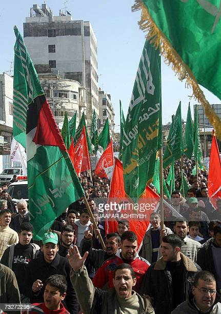 Supporters of rival Palestinian political parties Hamas and Fatah march together brandishing party and national flags and a portrait of late veteran...