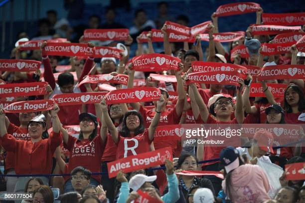 Supporters of Roger Federer of Switzerland raise banners during his men's 2nd round singles match against Diego Schwartzman of Argentina at the...