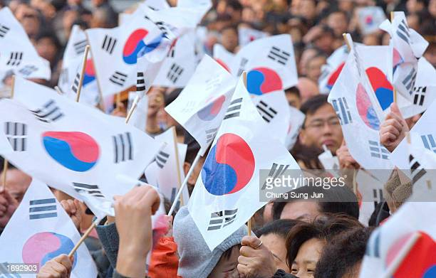 Supporters of Roh Moohyun South Korea ruling Millennium Democratic Party presidential candidate cheer as they hold South Korean National flags during...