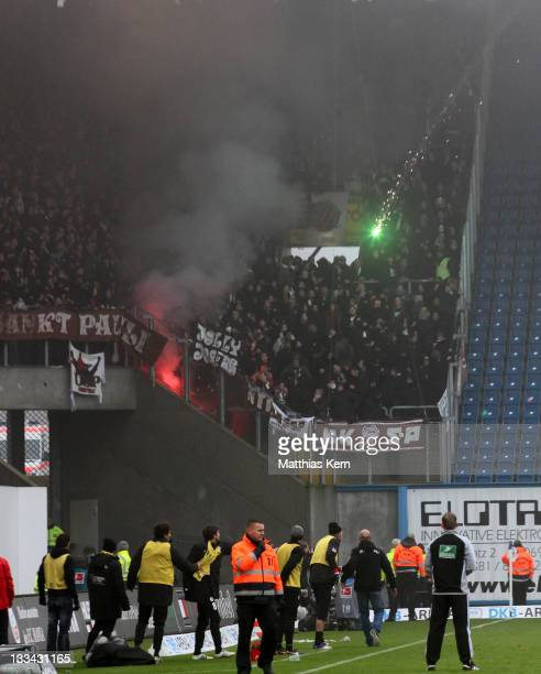 Supporters of Rostock shoot with pyrotechnic articles during the Second Bundesliga match between FC Hansa Rostock and FC St Pauli at DKB Arena on...
