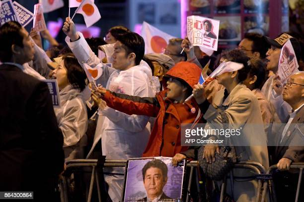 Supporters of ruling Liberal Democratic Party wave to the party leader and Japan's Prime Minister Shinzo Abe during his last stumping tour for the...