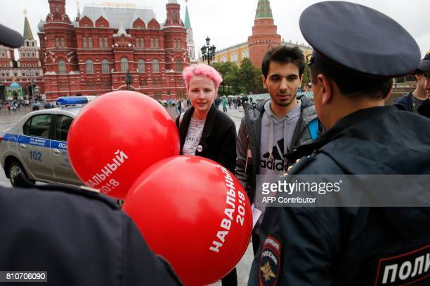 Supporters of Russian opposition leader Alexei Navalny hold balloons as they speak to police near the Kremlin in Moscow on July 8 a day after Navalny...