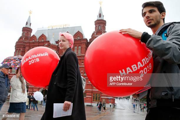 Supporters of Russian opposition leader Alexei Navalny holds balloons bearing Navalny's surname during an unauthorised action in central Moscow on...