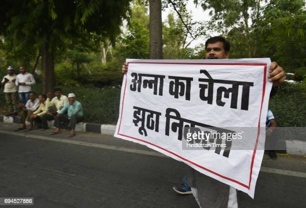 Supporters of sacked Aam Aadmi Party minister Kapil Mishra shout slogans and show banner during the AAP leaders'protest against Shivraj Singh's...