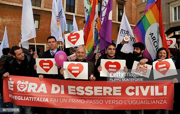 Supporters of samesex civil unions hold a banner reading 'It's time to be civil wake up Italy make the first step towards equality' as they...