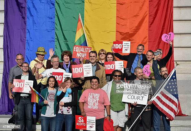 Supporters of samesex marriage stand for a photograph in front of a rainbow flag displayed at City Hall after the US Supreme Court ruling in San...