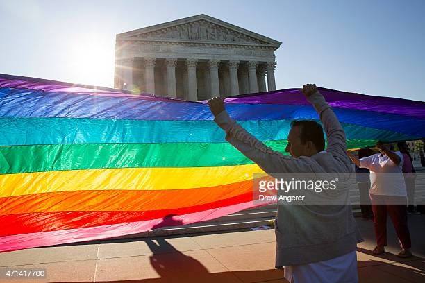 Supporters of samesex marriage unfurl a large rainbow pride flag near the Supreme Court April 28 2015 in Washington DC On Tuesday the Supreme Court...