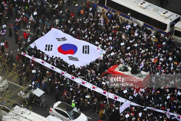 Supporters of scandalhit President Park GeunHye carry a big South Korean flag as they march during a protest calling for the nullification of the...