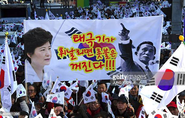 Supporters of scandalhit President Park GeunHye hold a large banner with a slogan that shows portraits of President Park and her father former...